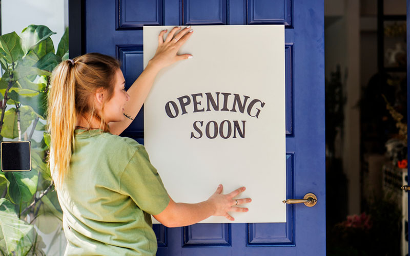 employee of a start-up holding opening soon sign